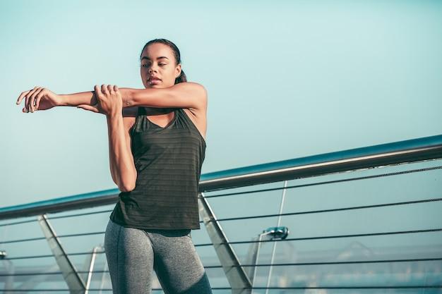 Atleta tranquila de pie junto a la barandilla y calentando sus músculos