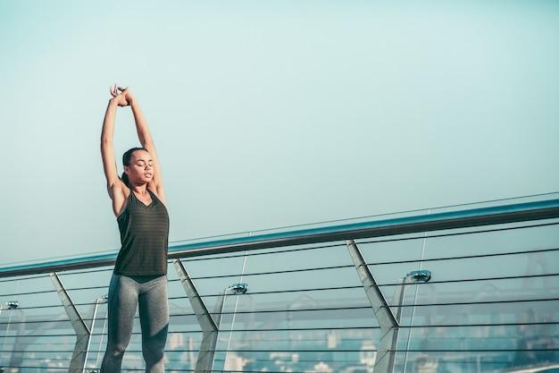 Atleta tranquilo de pie en el puente con los ojos cerrados y estirando los brazos hacia arriba. banner del sitio web