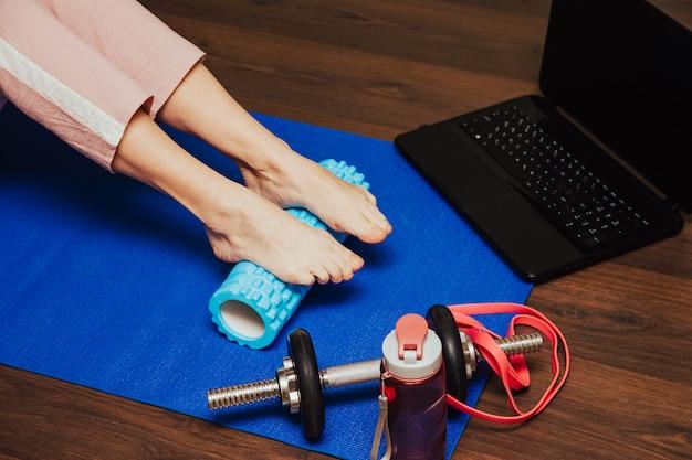 Atleta universitario que usa un rodillo de espuma para liberar sus músculos tensos