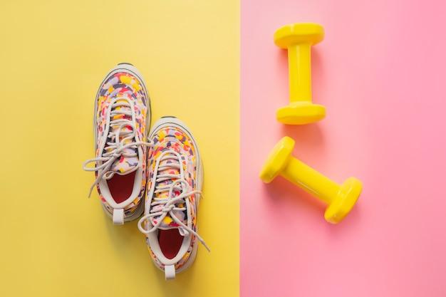 Atleta con zapatillas de deporte femeninas y pesas. concepto de aptitud equipos para gimnasio y hogar.