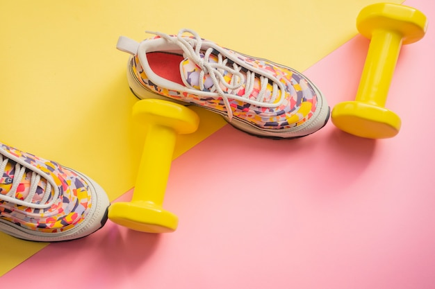 Atleta con zapatillas de deporte femeninas y pesas fondo amarillo-rosa. concepto de aptitud equipos para gimnasio y hogar.