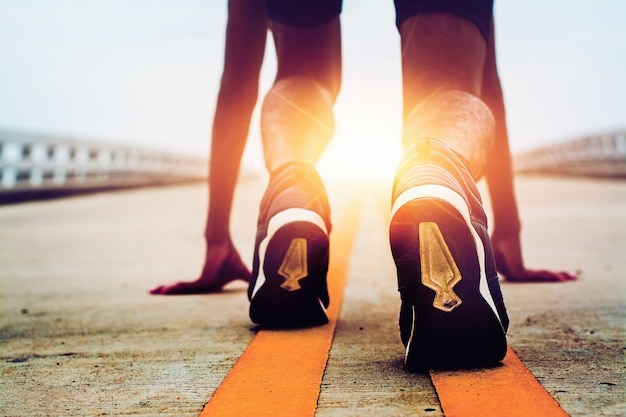 Los atletas comienzan en el camino con sol de la mañana.