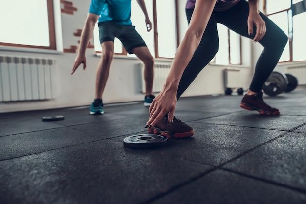 Atletas de crossfit tocando el peso de la barra en el gimnasio.