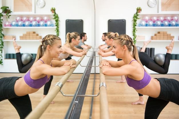 Atletas haciendo ejercicio con pelota con barra de gimnasio