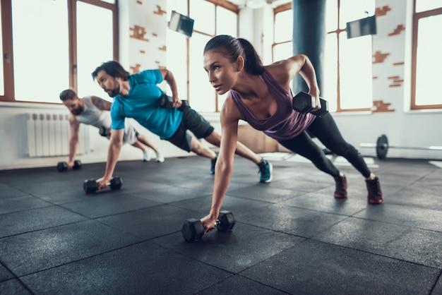 Atletas en el piso. levantamiento de pesas con una mano