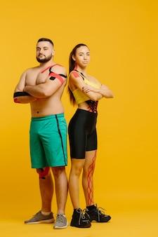 Atletas profesionales, hombre y mujer con cinta kinesiológica en el cuerpo, posando en amarillo