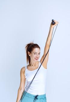Atlethic chica sosteniendo una cuerda de saltar azul.