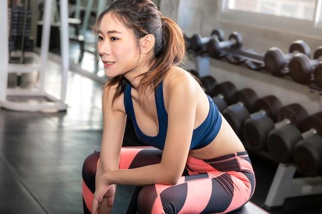 Atlética hermosa mujer en forma y saludable sonriendo en el gimnasio después del entrenamiento.
