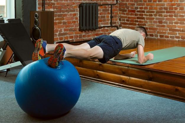 Atlético hombre haciendo ejercicios de equilibrio con la pelota de gimnasia