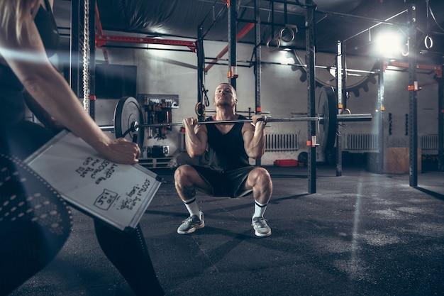 Atlético hombre y mujer con pesas