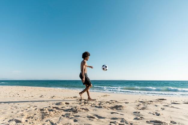 Atlético hombre pateando la pelota en la playa