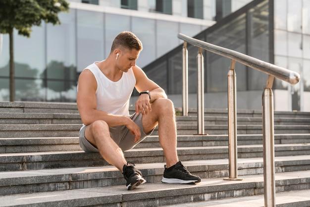 Atlético hombre sentado en las escaleras al aire libre