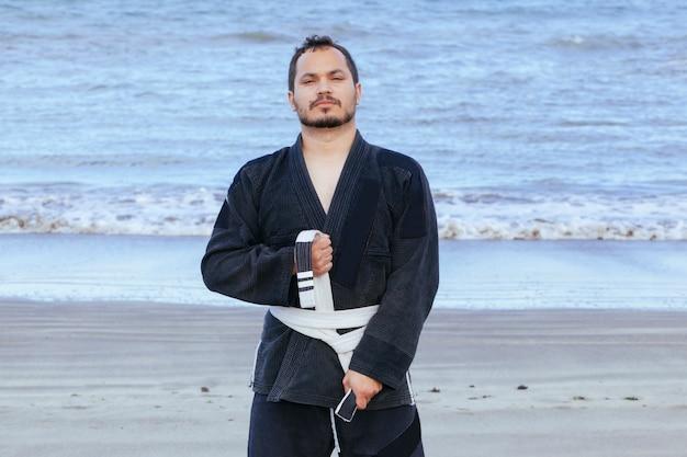 Atlético hombre vestido con un kimono de taekwondo aislado en la playa