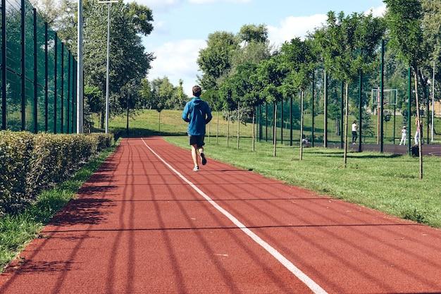 Atlético joven corriendo ejercicio de estiramiento por la mañana, bienestar y deporte