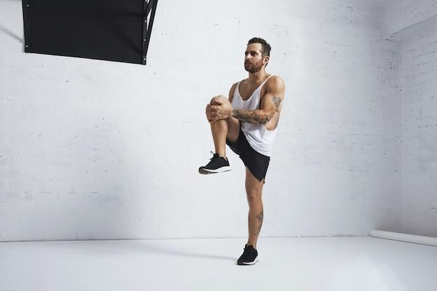 Atlético joven haciendo levantamientos de rodilla, estirando las piernas
