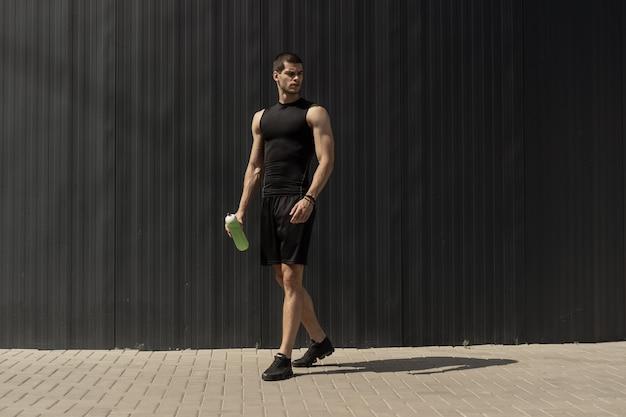 Atlético joven moderno posando en una pared metálica gris
