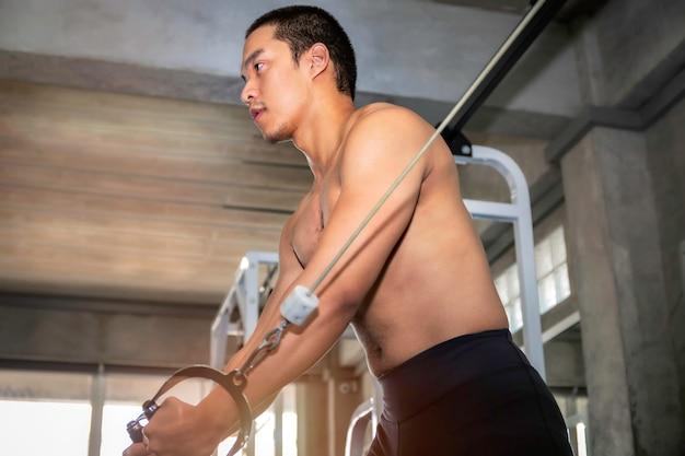 Atlético musculoso guapo asiático hombre entrenamiento cofre con cable en gimnasio