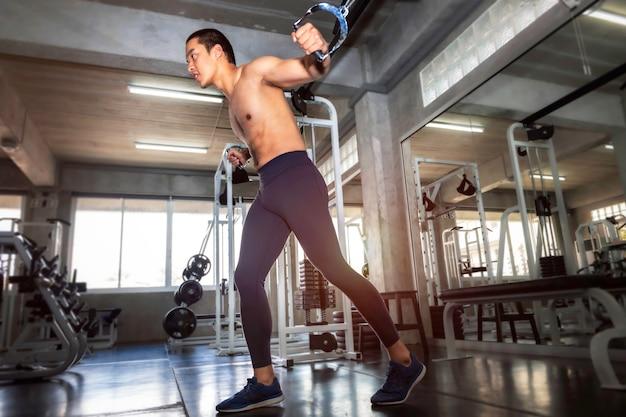 Atlético musculoso guapo hombre asiático entrenamiento pecho con cable en gimnasio.