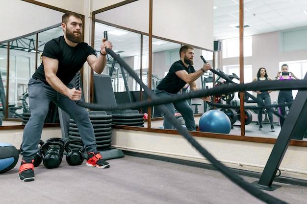 Atlético musculoso hombre barbudo haciendo ejercicio en el gimnasio con cuerdas de batalla