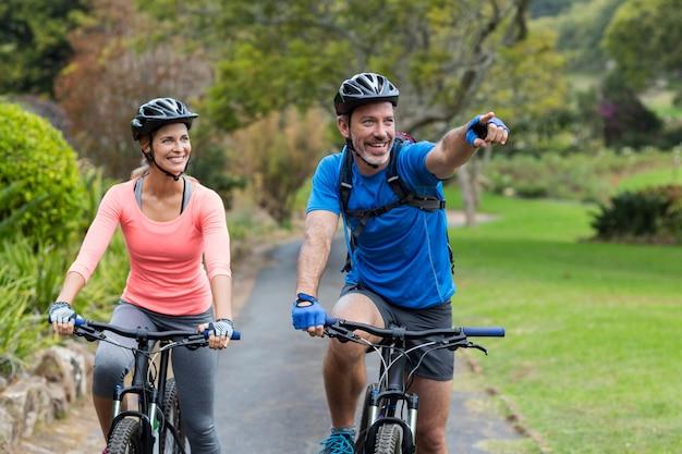 Atlético pareja apuntando mientras monta en bicicleta