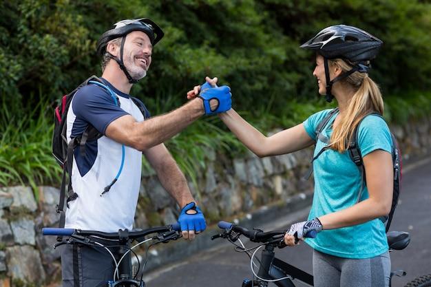 Atlético pareja cogidos de la mano mientras monta en bicicleta
