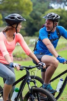 Atlético pareja mirando cara a cara mientras monta en bicicleta
