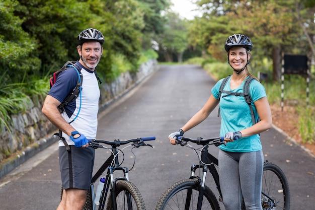 Atlético pareja de pie con bicicleta de montaña en la carretera abierta