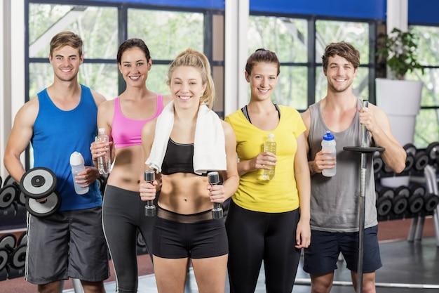 Atléticos hombres y mujeres posando en el gimnasio crossfit