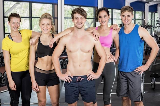 Atléticos hombres y mujeres trabajando en el gimnasio crossfit