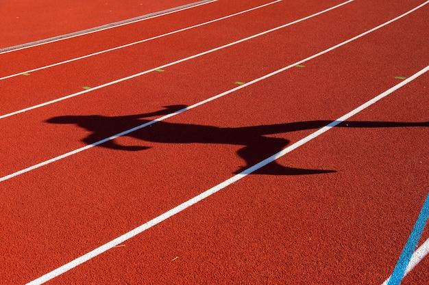 Atletismo, cinta de correr en un estadio con la sombra de un hombre
