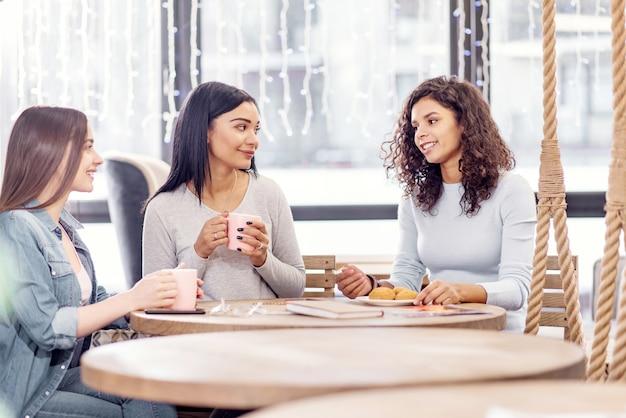 Atmósfera placentera. feliz feliz tres amigos bebiendo té mientras posan en el café y se comunican