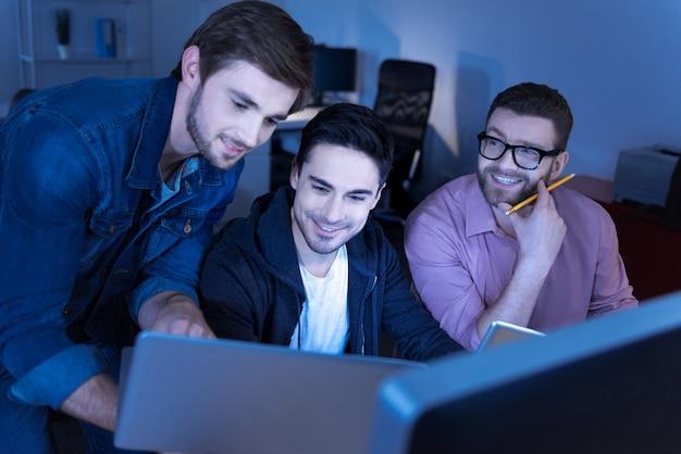 Atmósfera positiva. encantados programadores guapos guapos mirando la pantalla del portátil y sonriendo mientras se divierten con algo