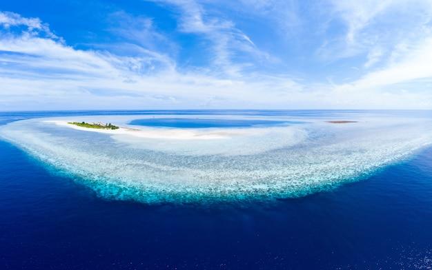 Atolón idílico aéreo, laguna azul y arrecife de coral turquesa