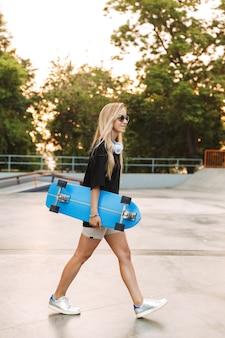 Atractiva adolescente funky llevando longboard mientras camina en el skatepark