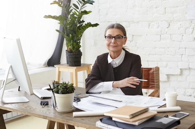 Atractiva arquitecta madura con gafas disfrutando del proceso de trabajo en una oficina espaciosa y luminosa, sentada frente a una computadora genérica, sosteniendo un lápiz, examinando dibujos y especificaciones en el escritorio