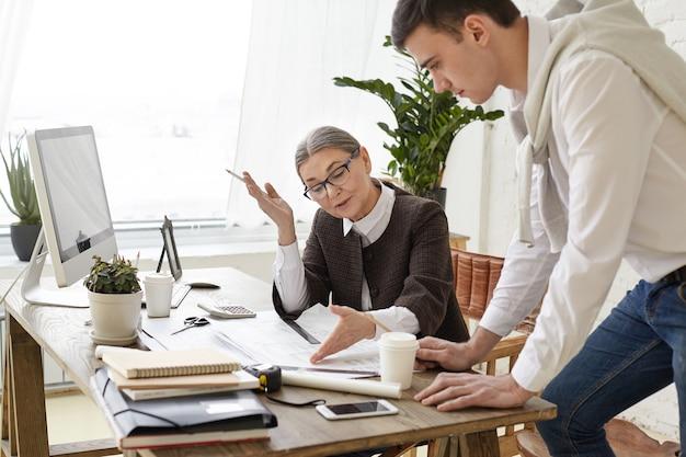 Atractiva arquitecta madura con gafas sentada frente a la computadora y revisando dibujos técnicos de su aprendiz, indicando inconvenientes, compartiendo sus ideas y visión. trabajo y cooperación