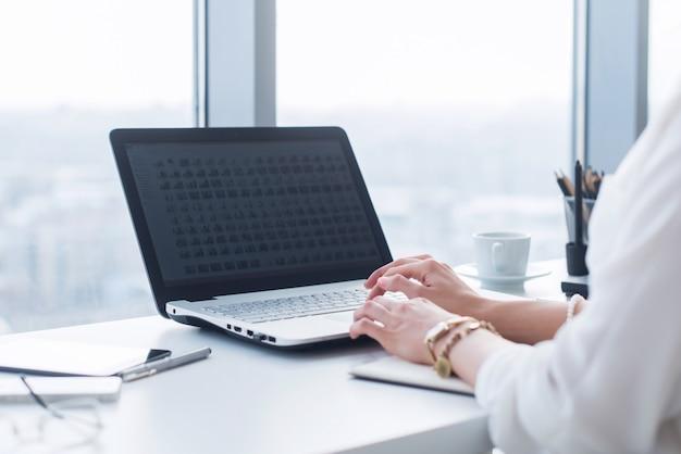 Atractiva asistente femenina trabajando, escribiendo, usando una computadora portátil, concentrada