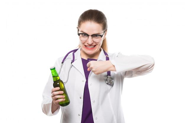 Atractiva caucásica morena doctora de pie en la oficina con una botella de cerveza en sus manos mostrando signos de prevención