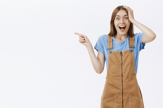 Atractiva chica alegre que señala con el dedo a la izquierda en el logo mirando impresionado