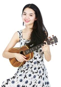Atractiva chica asiática tocando el ukelele