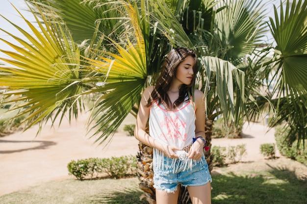 Atractiva chica delgada en pantalones cortos de mezclilla se esconde del sol bajo la palmera con expresión seria. adorable morena joven en camiseta sin mangas de moda descansando en el exótico parque de vacaciones