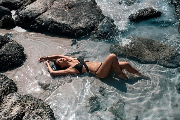 Atractiva chica delgada en traje de baño negro se relaja cerca del mar