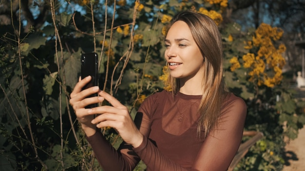 Atractiva chica elegante hablando felizmente con amigos en video chat mientras camina por el parque