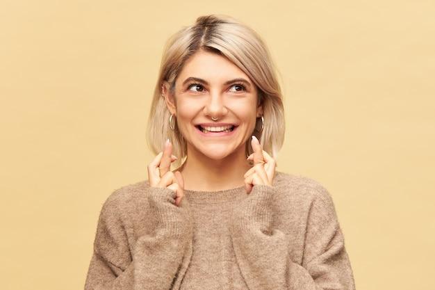 Atractiva chica estudiante elegante en acogedor suéter de cachemira manteniendo los dedos cruzados, esperando obtener los mejores resultados en la prueba o examen. esperanza joven rubia cruzando los dedos para la buena suerte