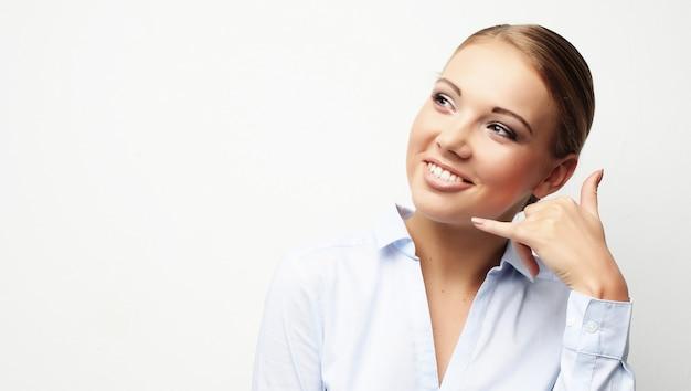 Atractiva chica feliz gesticulando con los dedos llámame