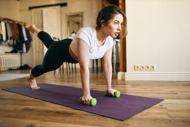 Atractiva chica en forma haciendo plancha con mancuernas mientras hace ejercicio en la alfombra en la sala de estar