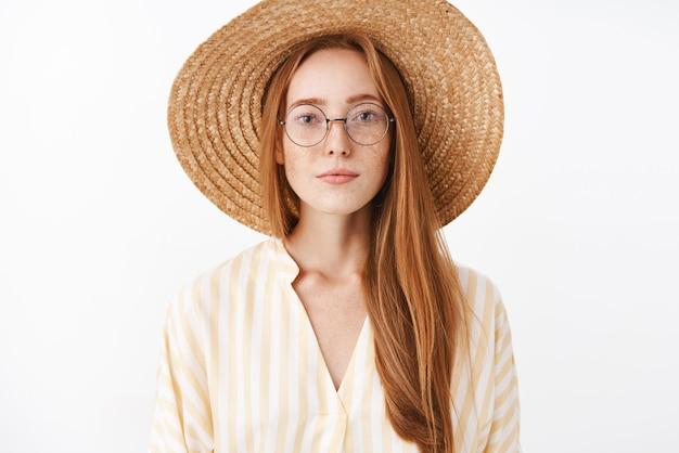 Atractiva chica hipster con estilo con cabello pelirrojo y pecas en gafas de moda sombrero de paja y blusa linda amarilla sonriendo con expresión despreocupada complacida asistiendo a una conferencia interesante en el café