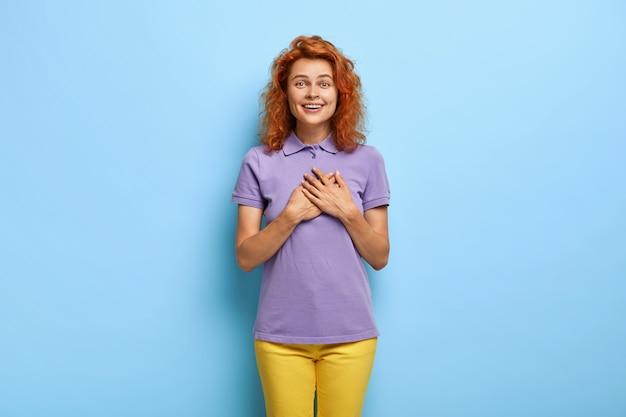 Atractiva chica de jengibre presiona las manos sobre el pecho, siente gratitud