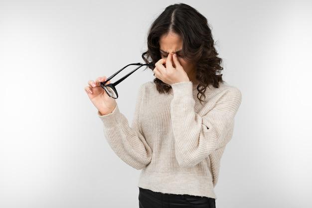 Atractiva chica morena entrecierra los ojos con gafas en la mano en un gris con espacio de copia
