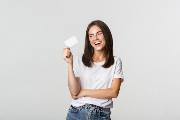 Atractiva chica morena feliz riendo y sosteniendo la tarjeta de crédito, blanco.
